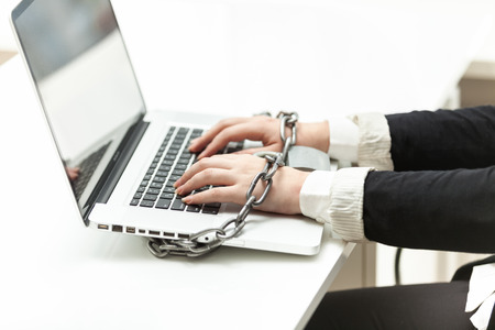 Closeup photo of businesswoman locked to laptop by chain photo