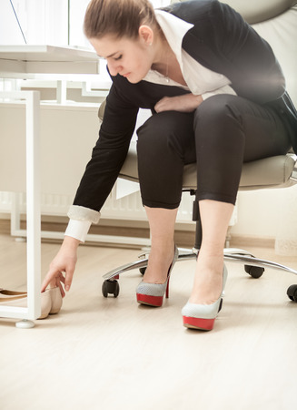 Beautiful businesswoman changing shoes under table at office photo