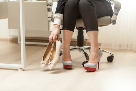 Closeup photo of businesswoman changing shoes under table photo