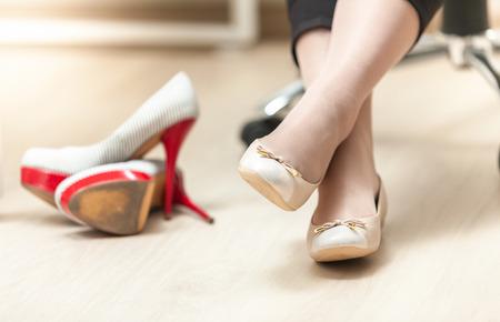 Foto del primer de la mujer con zapatillas de ballet en lugar de tacones altos