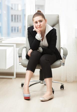 high heeled shoe: Sad businesswoman choosing between high heeled shoe and ballet flat Stock Photo
