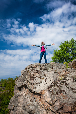 stretched out: Outdoor photo of beautiful woman standing on top of high cliff with stretched out hands Stock Photo