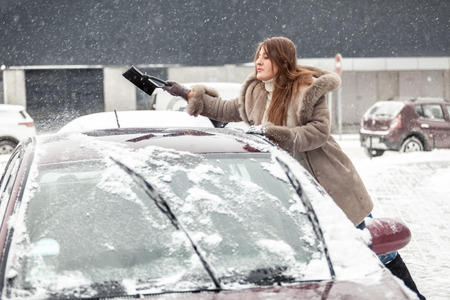 Portrait of young woman cleaning snow from car roof using brush