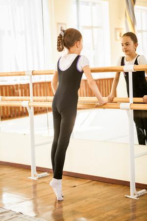 Kleines Mädchen auf den Fußspitzen bei Tanzkurs in der Nähe von Spiegel stehend