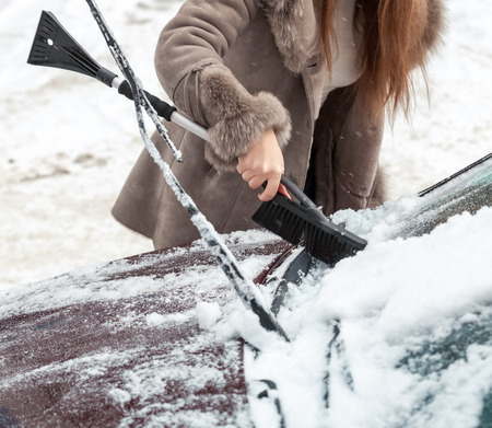 Closeup photo of woman cleaning snow from car hood with brush photo