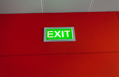 Green exit sign glowing on red wall photo