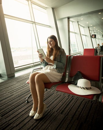 computer devices: Young woman using digital tablet while waiting for airplane departure