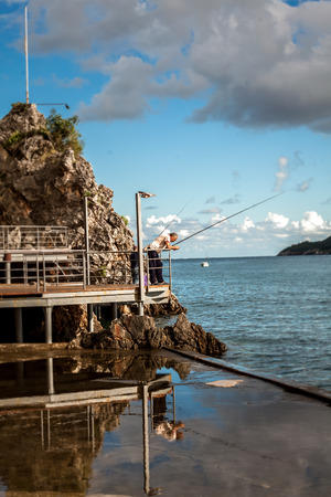 Old fisherman standing with rod on wooden pier at rocky shore photo