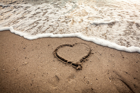 romantic background: Toned photo of heart drawn on sand being washed by sea wave