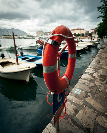Red lifebuoy hanging in sea port at rainy day