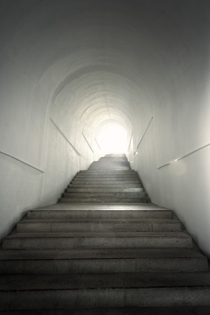 stone of destiny: Light of the end of tunnel with ascending stairs Stock Photo