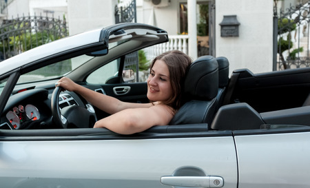 Portrait of beautiful smiling woman sitting in convertible and holding steering wheel photo
