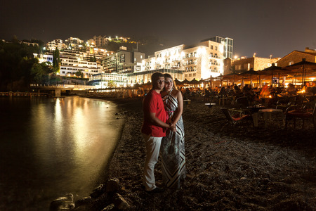 Beautiful romantic couple hugging at night on beach of Montenegro photo