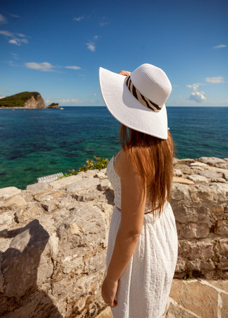 Closeup portrait of beautiful woman in white hat looking at sea photo