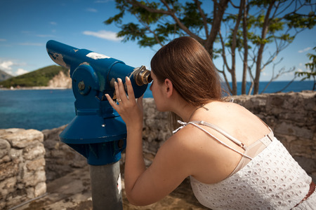 touristic: Young woman looking on landscape through touristic coin operated telescope Stock Photo