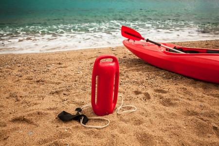 life saving: Closeup photo of life saving buoy and lifeguard kayak on sand beach