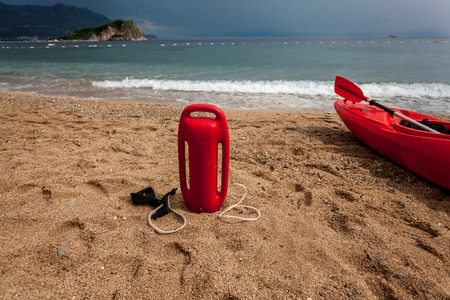 Photo of red lifebuoy and lifeguard canoe on sandy beach at stormy day photo