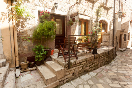 Narrow street of old town decorated with pots and flowers photo