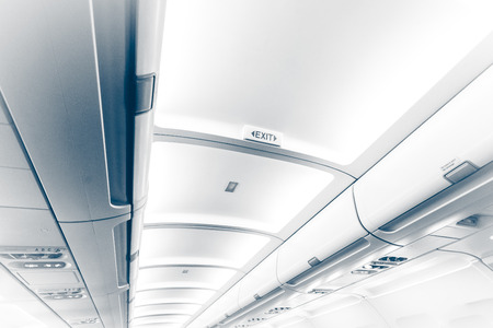Toned photo of long ceiling in airplane with exit sign photo