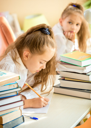 write off: Portrait of concentrated girl doing homework while classmate trying to write off
