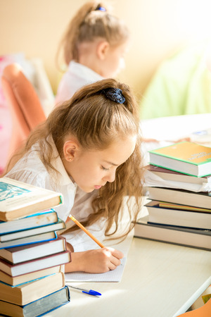 Portrait of brunette girl sitting in class and writing in exercise book photo