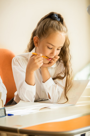 Closeup portrait of schoolgirl chewing pencil while doing homework photo