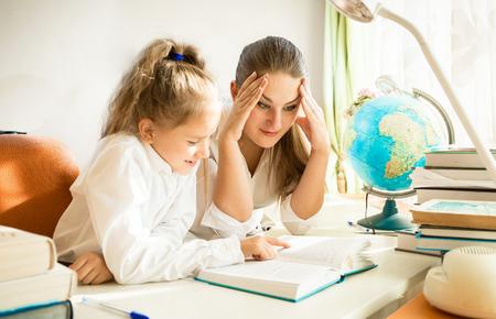 Portrét zmateně matky při pohledu na dcery složité domácí úkoly