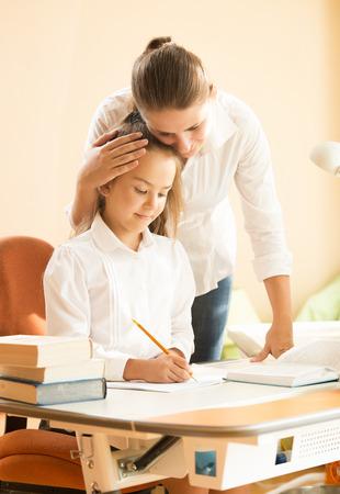 deberes: Retrato de la madre joven hija alabando hacer la tarea en el escritorio