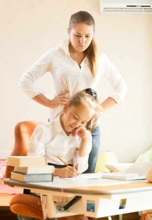 Young mother watching at daughter doing homework photo