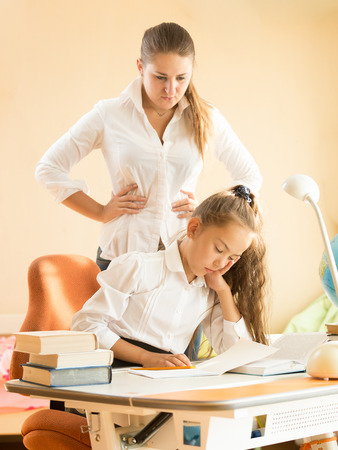 Young mother being angry of daughter sleeping on desk while doing homework photo