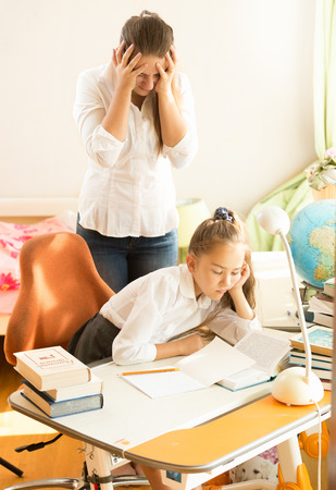 angry: Frustrated young mother looking daughter sleeping while doing homework Stock Photo
