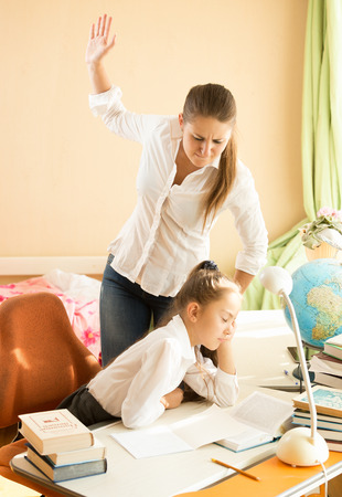 Angry mother giving a cuff on nape to daughter sleeping while doing homework photo