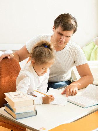 Young man pointing on mistake at daughters notebook Stock Photo