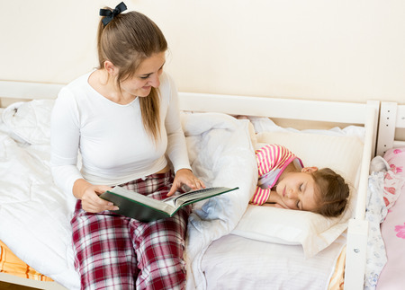 Young mother sitting on bed next to daughter and reading a story