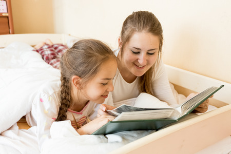 Portrait of mother reading big old book to daughter at bed photo