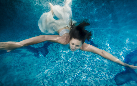 Beautiful brunette woman in white dress swimming underwater at pool photo