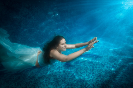 pool diving: Underwater shot of beautiful woman in dress comes up from pool at beam of light Stock Photo