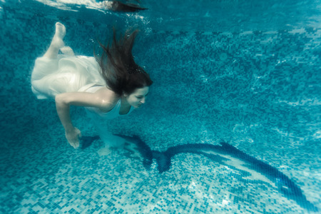 Beautiful shot of sexy woman in white cloth diving underwater at pool photo