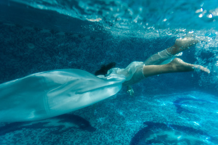 Underwater shot of beautiful woman wearing white fabric diving in pool photo
