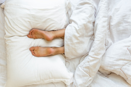 Closeup view of feet lying on soft white pillow at bed Stockfoto