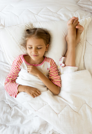 Indoor photo of girl lying next to sisters feet on pillow photo