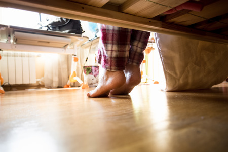 laying: Photo from under the bed on barefoot woman in pajamas at morning Stock Photo