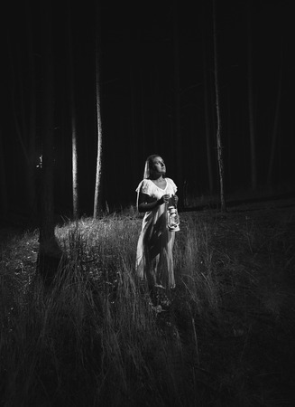 Black and white photo of woman in white dress walking at forest at night with lamp