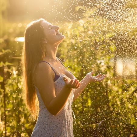 caucasian water drops: Portrait of beautiful woman enjoying rain at sunny day at garden