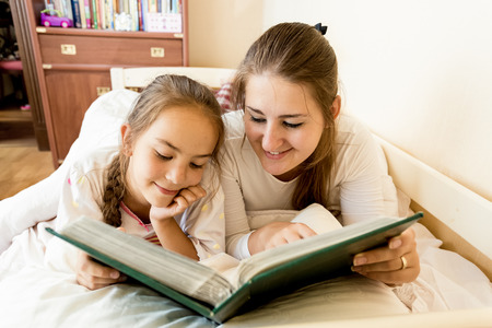 Closeup portrait of young mother and daughter lying in bed and viewing photo album photo