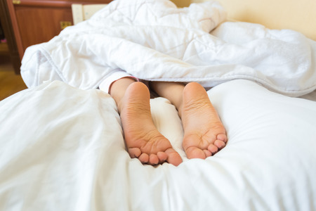 Funny photo on bed of girls feet lying on pillow