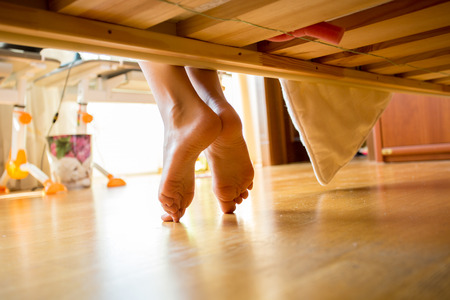 barefeet: Closeup shot of female feet under bed at morning