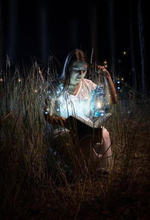 Portrait of smiling woman in nightgown sitting at field at night and reading book photo