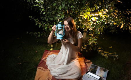 Beautiful young woman looking at old lantern while sitting at night garden photo