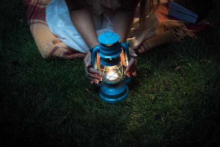 candil: Primer disparo de la mujer sentada en el césped por la noche y de la mano en la linterna Foto de archivo
